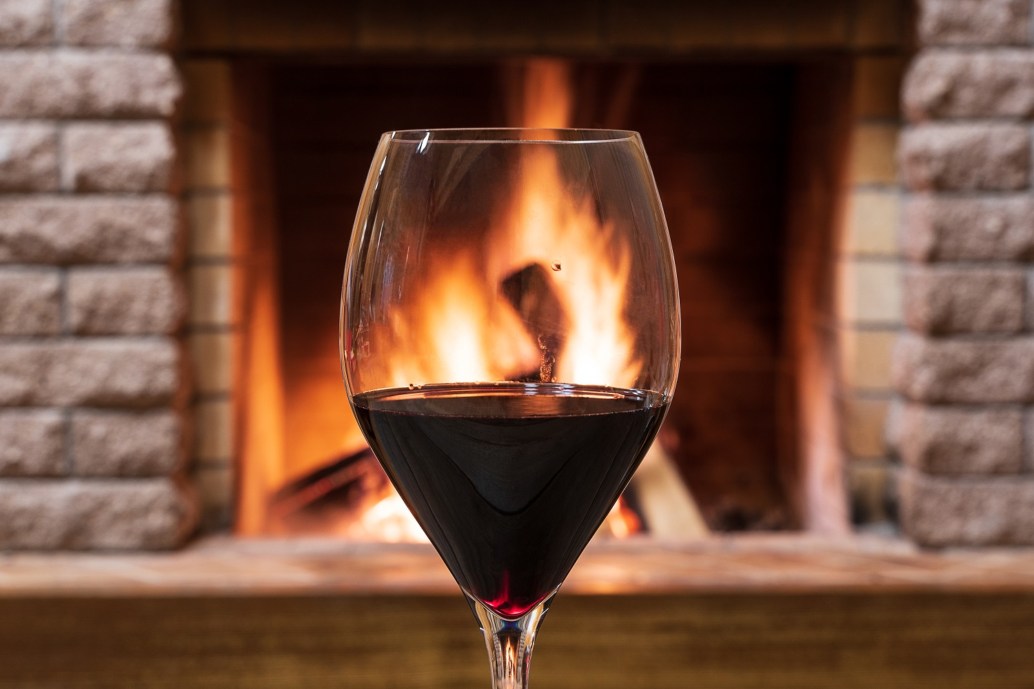 Glass of wine against cozy fireplace background, hygge concept.